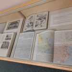 Various books on China with black and white pictures, a map, and a comic book.