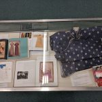 Books about Chinese dress along with a folded blue dress.