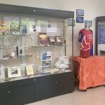 Display cases fileld with books, leis, and artifacts for the Te Moana Nui exhibit