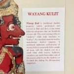 A shadow puppet next to a description of Wayang Kulit traditional shadow puppetry