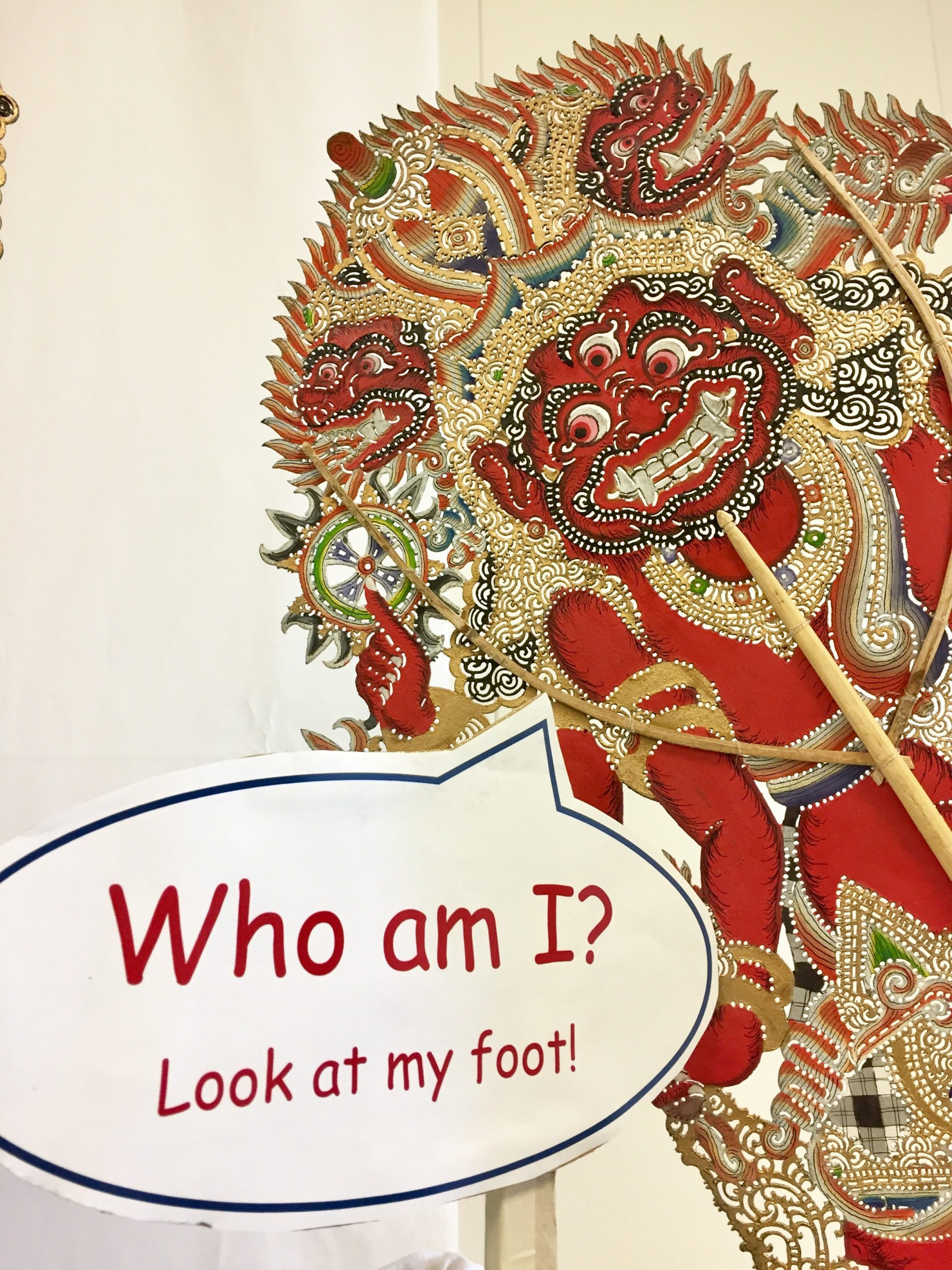 A shadow puppet with speech bubble Who am I? Look at my foot!