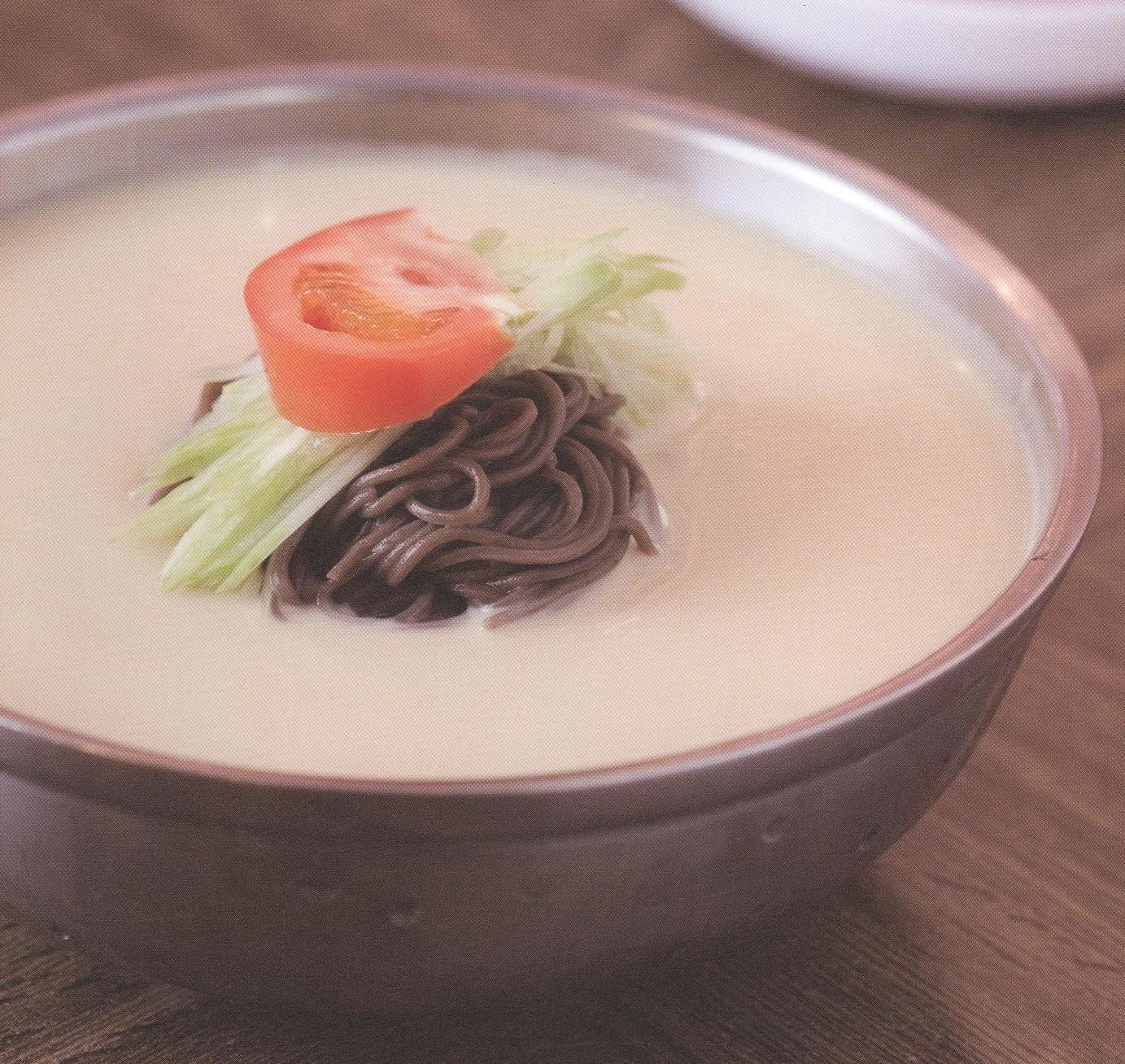 Dark noodles in a white sauce with a tomato slice on top