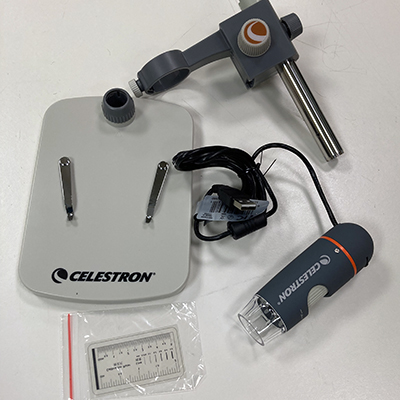 Photograph of Celestron microscope, showing base, USB wire, and calibrating ruler