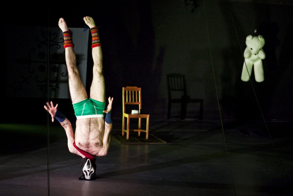 Man standing on his head with green undies and mask. White teddy bear floating on the side.