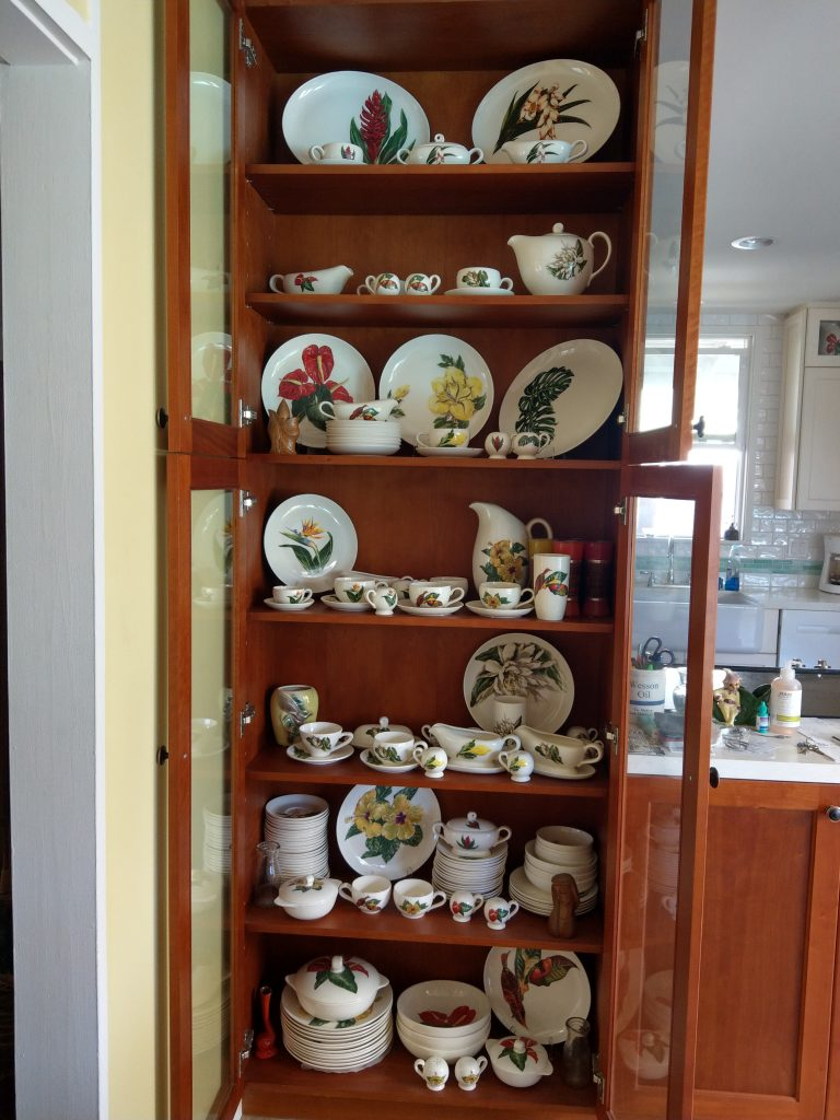 Cabinets with glass doors open to show eight shelves full of various types of cups, plates, bowls, pitchers, tea cups, etc. with painted tropical flowers on them. Part of a kitchen can be seen in the right side of the image.