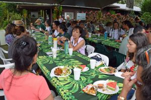 partygoers sit and eat together under a large tent