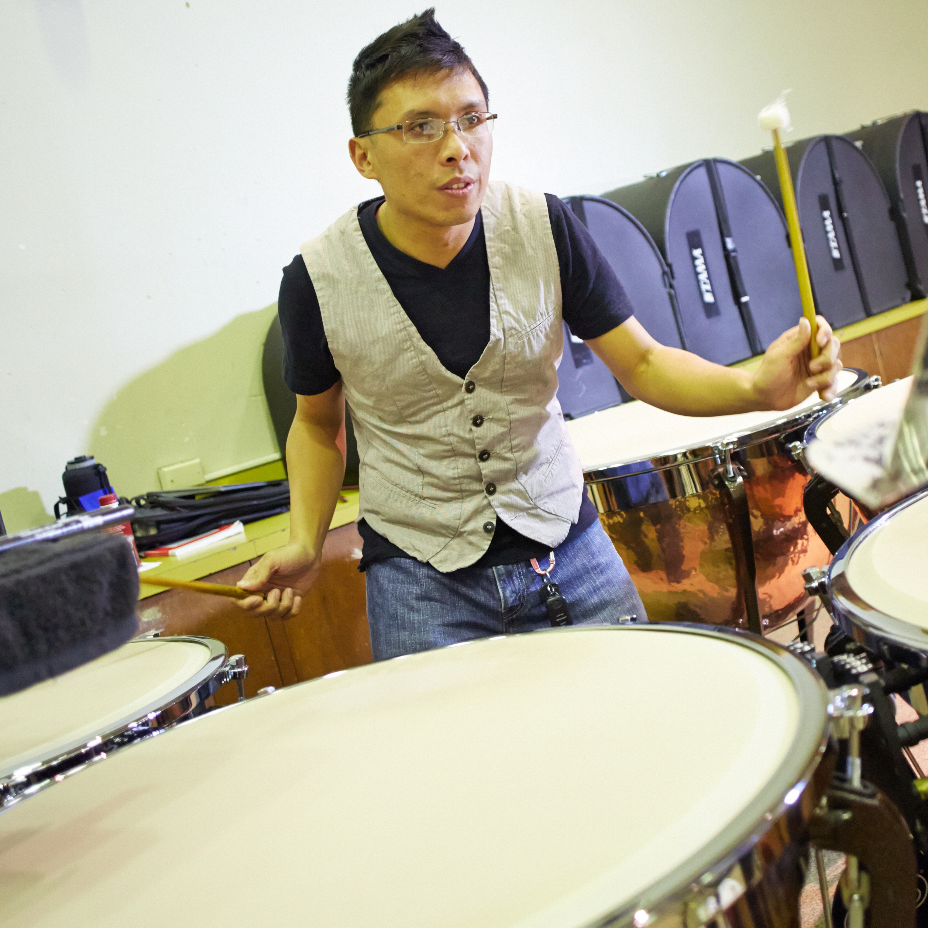 Student Frederick Mariano playing timpani during a Wind Ensemble rehearsal.