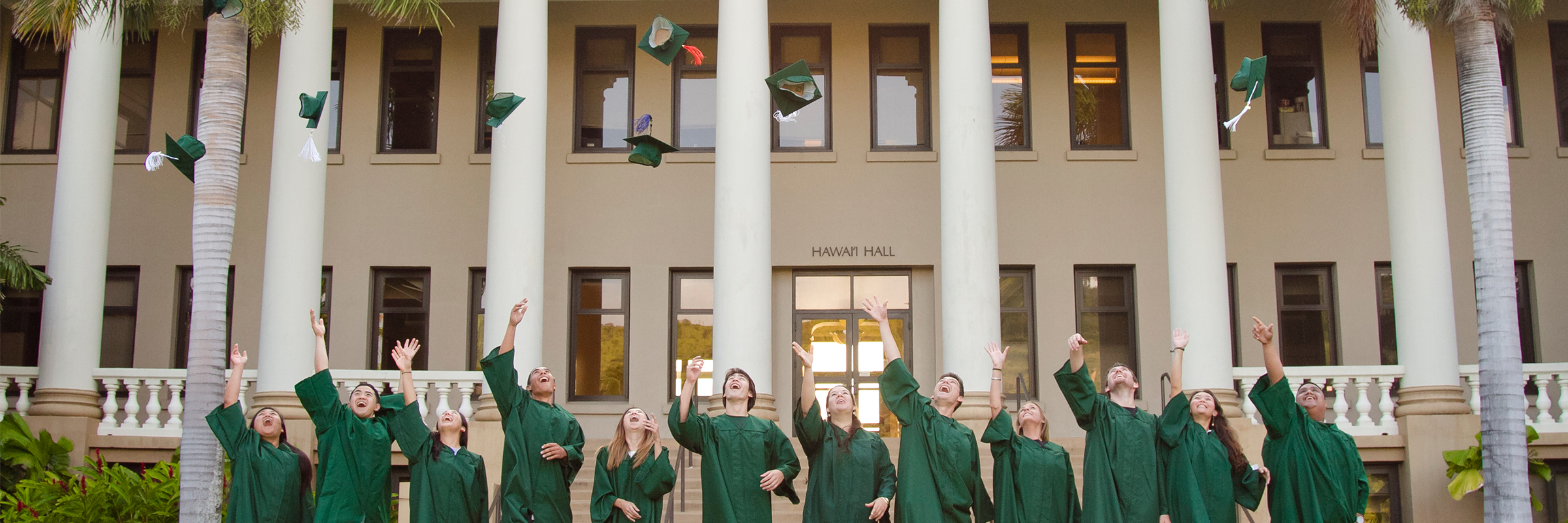 Students in green graduation gown are throwing up their caps in front of Hawaii Hall