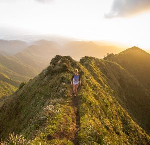 Woman Walking On Trail In The Mountains At Sunset