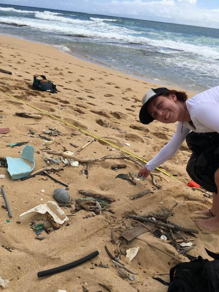 UROP student, Kayla Brignac, picking up litter on the beach.