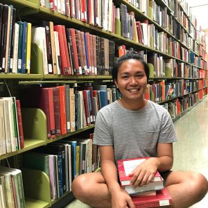 UROP student, Jeremiah Bonilla, in a library with a stack of books needed for her project.