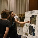 A student explains an image on her poster to a faculty guest at the 2019 SURE Symposium